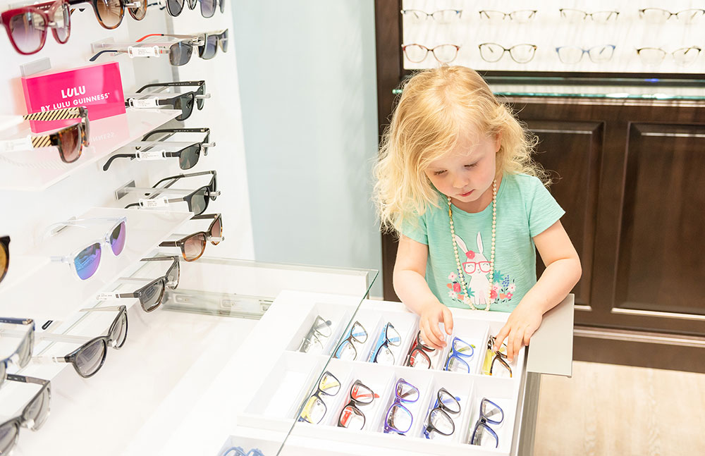 Girl child pediatric looking at eyeglasses at Wauseon Eye Care